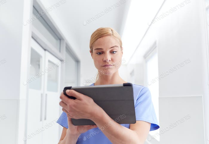 Female Doctor Wearing Scrubs In Hospital Corridor Using Digital Tablet