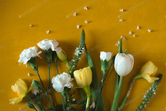 Tulips and carnations on a yellow table