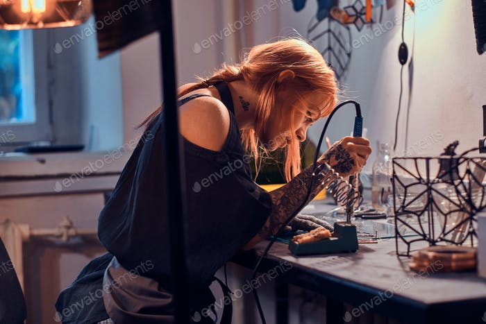 Attractive woman is doing soldering at her own artisan lamp studio.