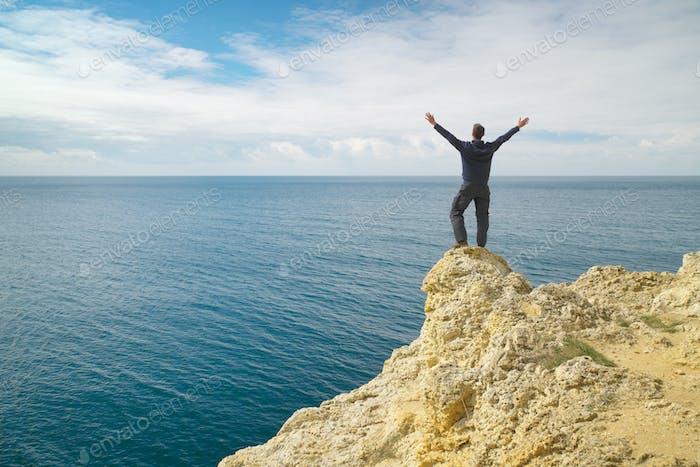Man on sea cliff edge.