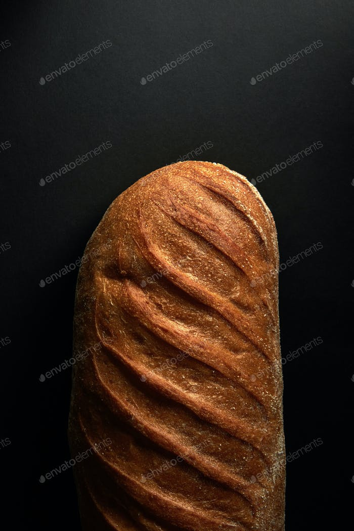Freshly baked healthy white bread on a black background with copy space. Top view