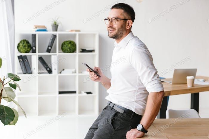 Изображение исполнительного директора мужчины в формальной одежде, сидящего на столе