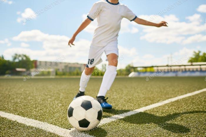 Boy in Uniform Kicking Ball on Football Field