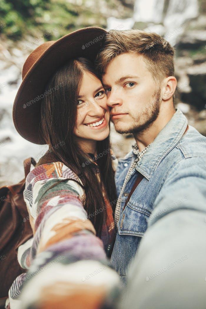 stilvolle Hipster Paar nehmen Selfie und lächelnd bei Wasserfall im Wald