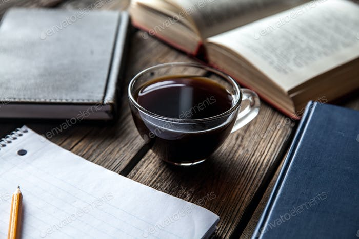 Bücher und eine Tasse Kaffee auf einem hölzernen Hintergrund