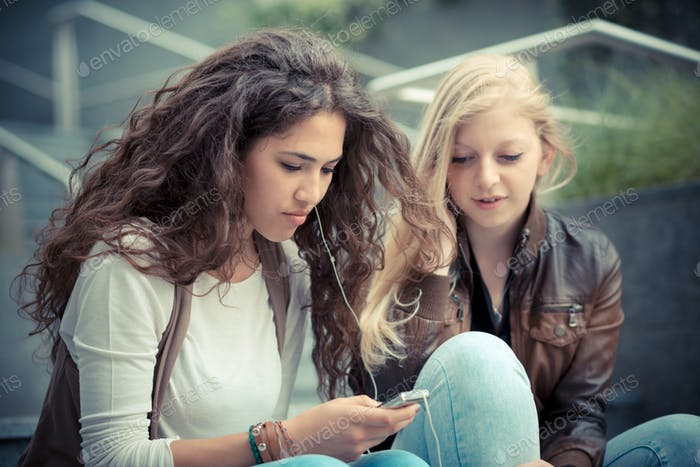 blonde and brunette beautiful stylish young women using smart ph