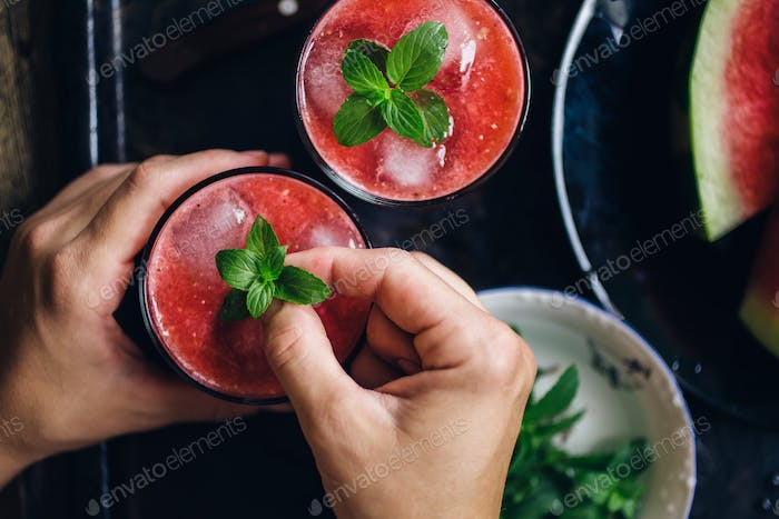 Person decorates red smoothie