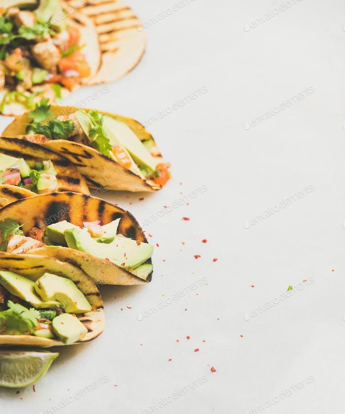 Healthy corn tortillas with grilled chicken, avocado, lime, copy space