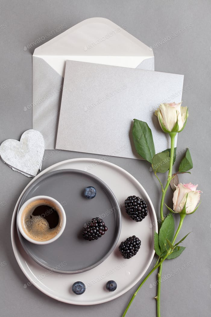 Top view over coffee cup, and gray postcard with envelope