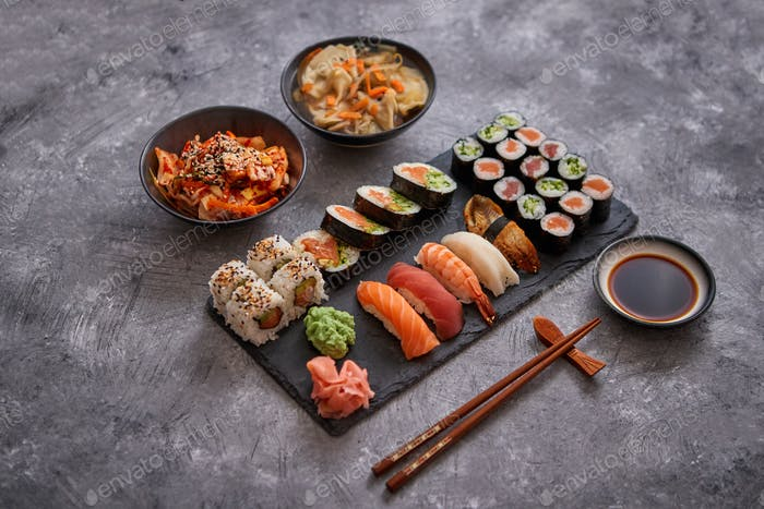 Various kinds of sushi placed on black stone board