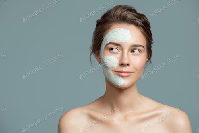 Porträt von Schöne Frau mit blau Creme Maske auf Ihr Gesicht.