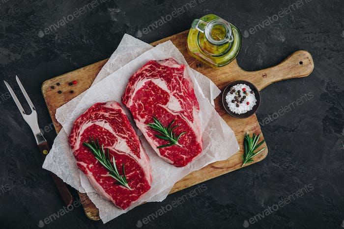 Ribeye Steak, rohes frisches Rindfleisch mit Salz und Rosmarin bereit zum Grillen