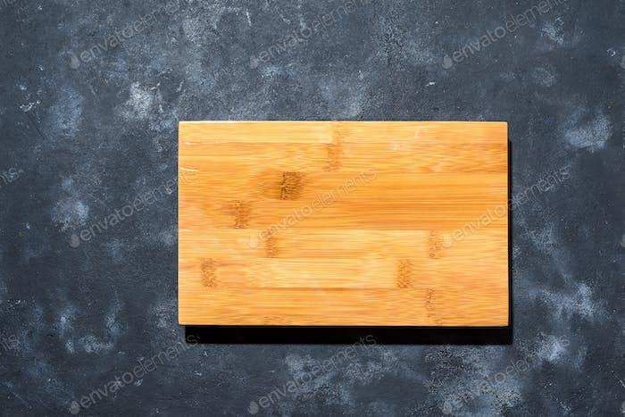 Top View helle leere Schale aus Holz auf schwarzem Steinbrett Hintergrund, Kopierraum