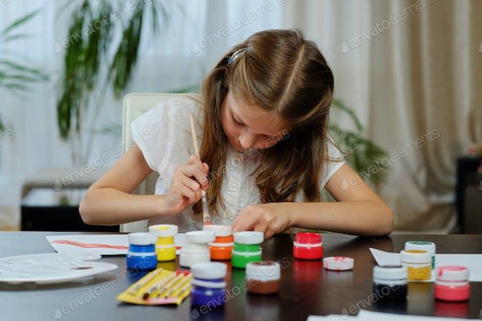 Una chica pintando con pintura acrílica.