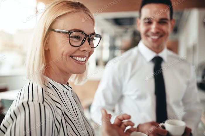 Lächelnde Geschäftsfrau im Gespräch mit Kollegen über Kaffee in einem Büro