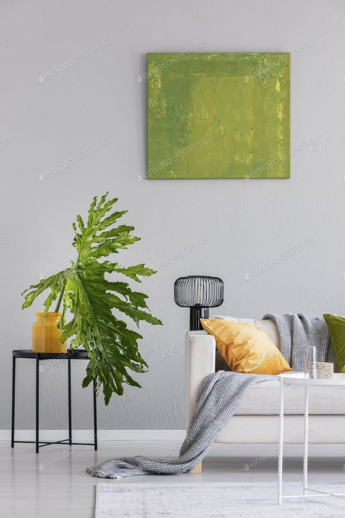 Plant on table next to settee with lamp and blanket in grey loft