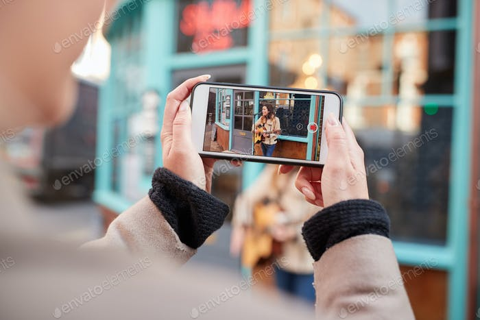 Person Filming Female Musician Busking Playing Acoustic Guitar And Singing To Crowd On Mobile Phone