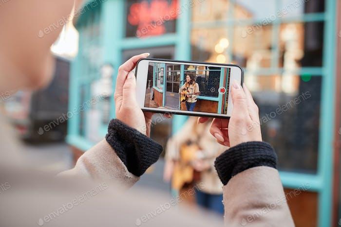 Person Dreharbeiten weiblicher Musiker Busking Spielen Akustikgitarre Und Singen An Masse Auf Handy