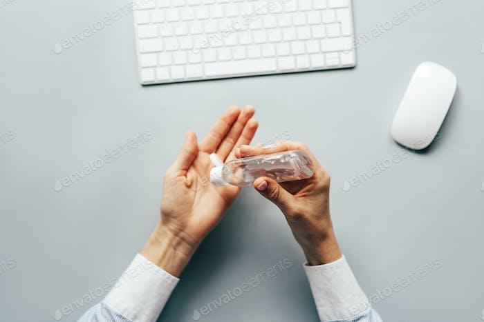 Nahaufnahme der Hände mit antiseptischem Gel, um die Hände über einen Arbeitstisch zu desinfizieren.