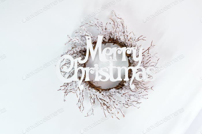 letters Merry Christmas and wreath branches of frost on white background with sunlight rays, flat