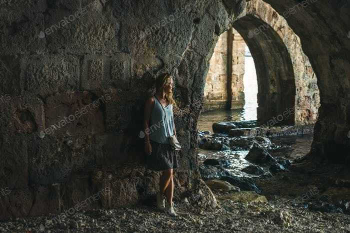 Young blond tourist woman stading in ancient stone shipyard