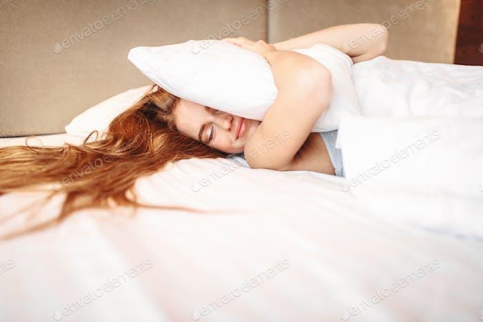 Beautiful woman hugs pillow, waking up