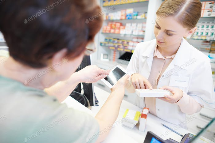 Customer using cell phone at pharmacy checkout