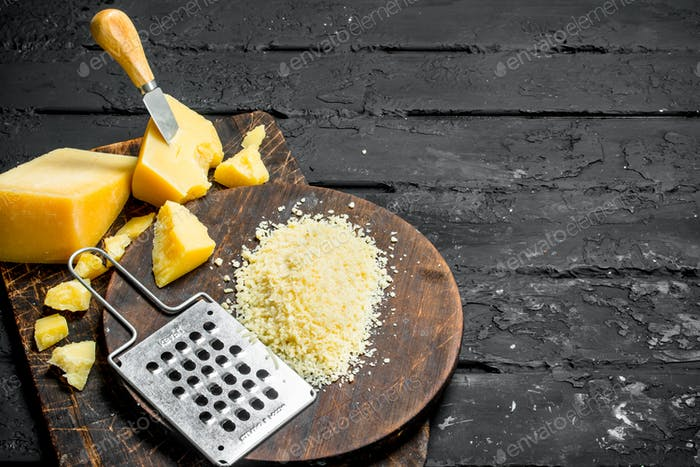 Grated Parmesan cheese on a wooden Board.