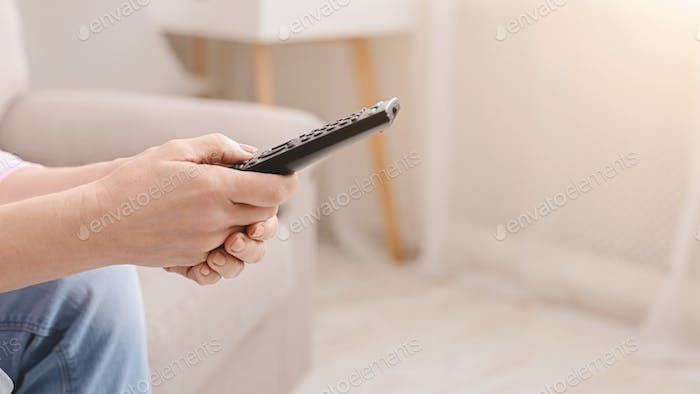 Remote control in hands of senior woman, close up