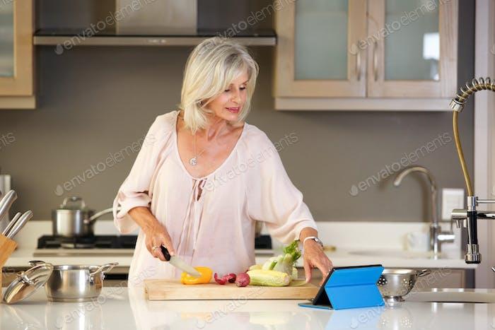 ältere Frau in der Küche Lesen Rezept auf Tablette