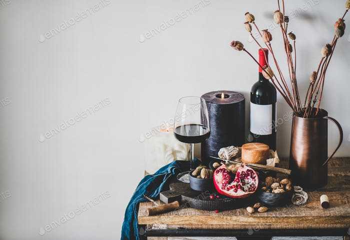 Red wine and different snacks on wooden board, copy space