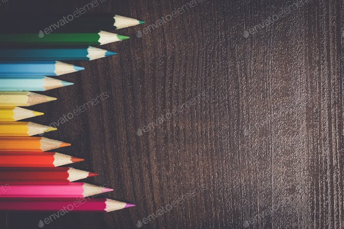 colorful pencils on dark brown table