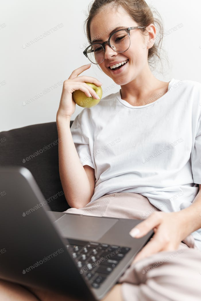 Image of smiling young woman holding apple and using laptop