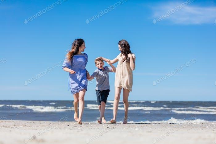 Mutter und ihre Kinder machen einen Spaziergang am Meer.