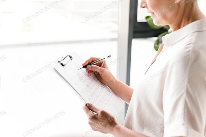 Close up of mature business woman taking notes