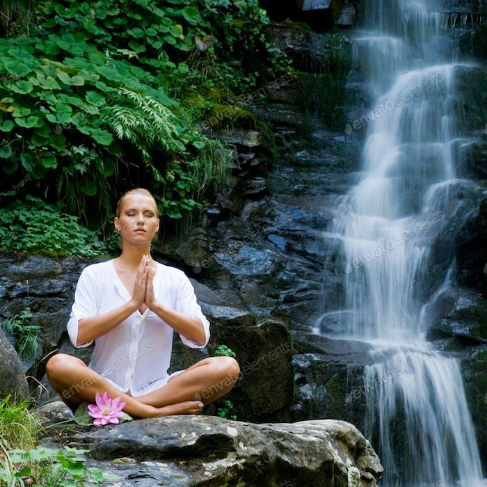Молодая женщина делает йогу возле водопада