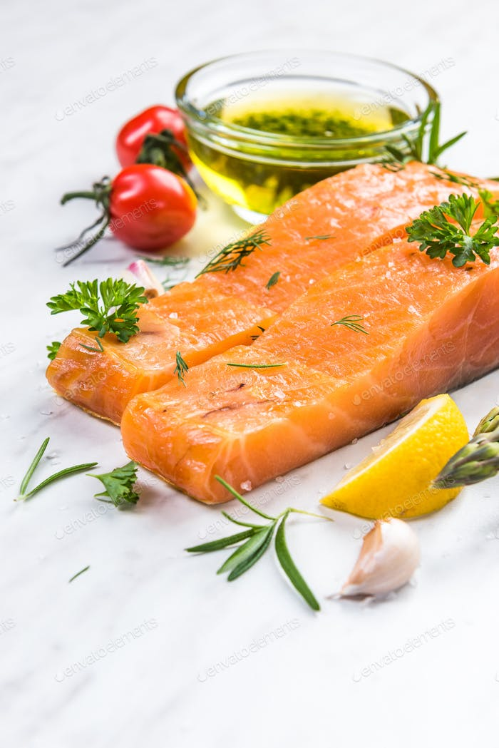 Preparing fresh salmon fish slices with olive and spices