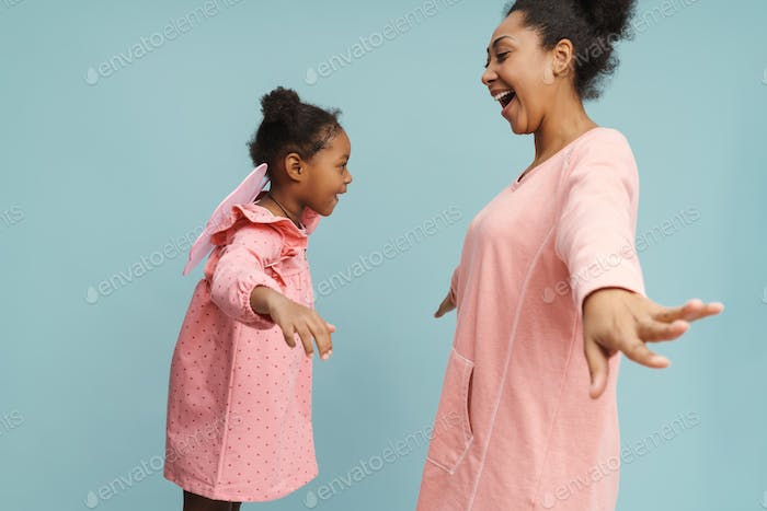 Happy black mother and daughter with butterfly wings making fun together