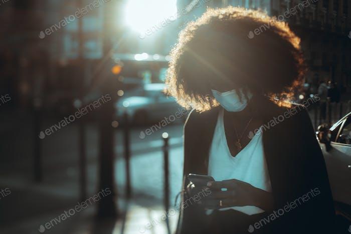 Black phoning girl in antivirus mask