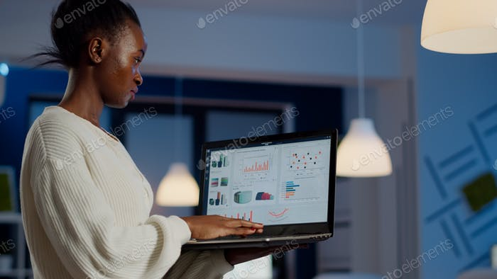 African freelancer typing on laptop late at night standing in start up office