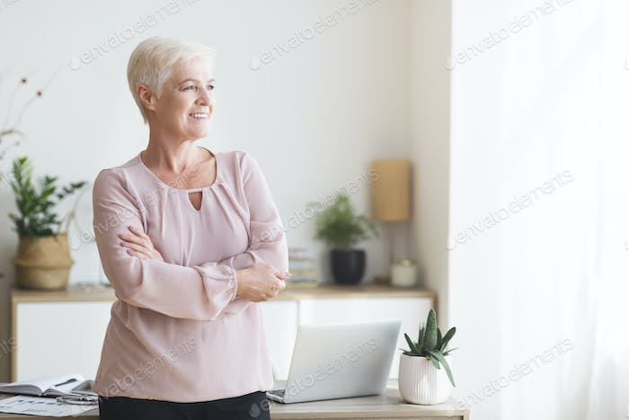 Satisfied elderly business woman looking at window