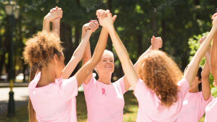 Breast Cancer Survivors Standing Holding Hands In Park, Panorama