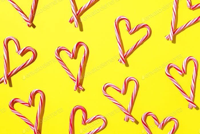 Pattern with hearts made of Christmas candy canes on yellow background. Top view. Flat lay. Love