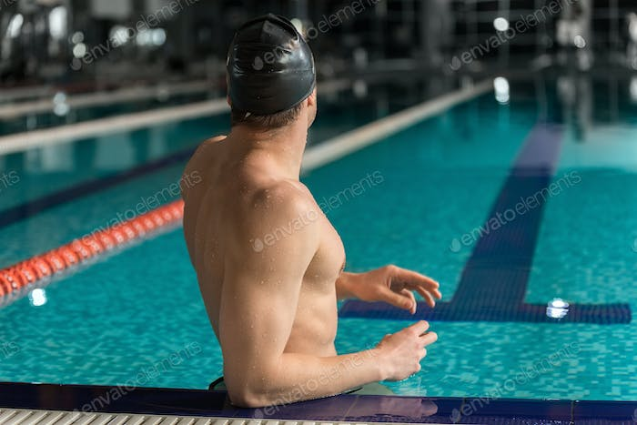 Rear view of a male swimmer standing