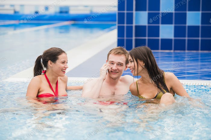 Smiling people with cell phone in swimming pool making call. Health, relaxation and communication