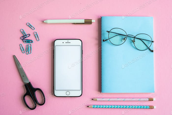 Smartphone, scissors, notebook with eyeglasses, clips, pen and pencils