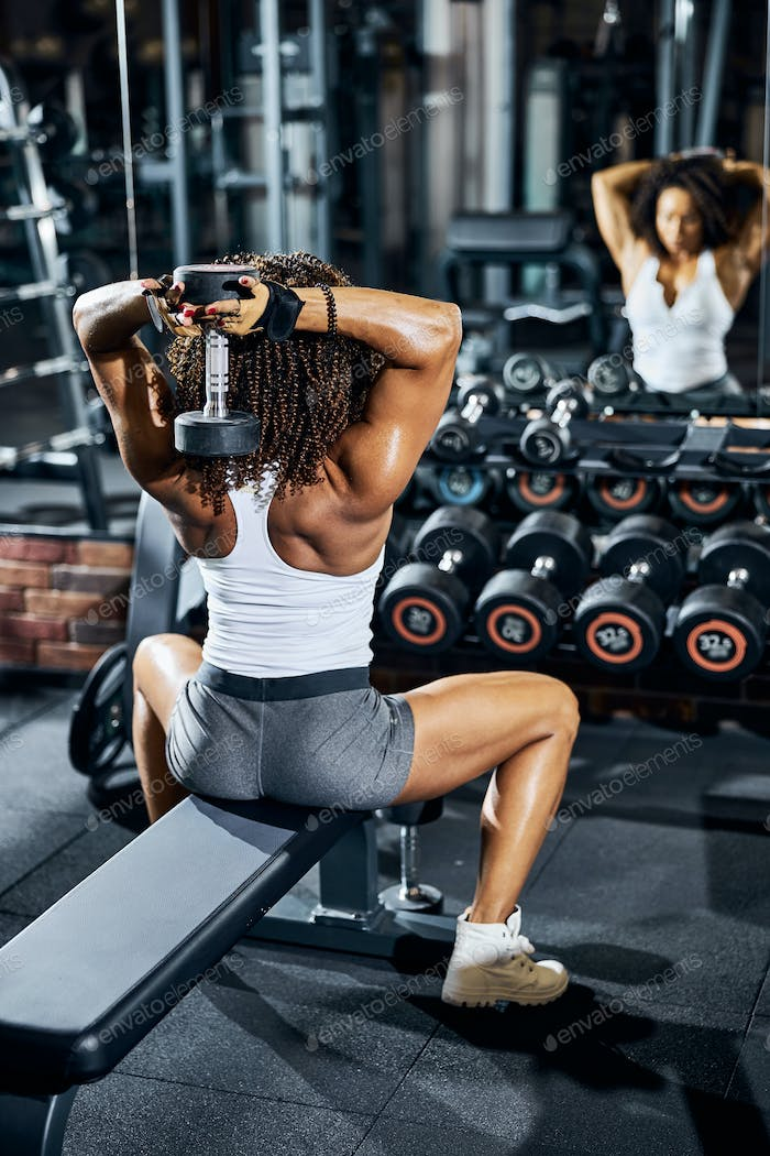 Female bodybuilder working out in front of the mirror