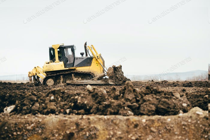 mini industrial bulldozer moving dirt and earth with scoop. Industrial details of landscaping