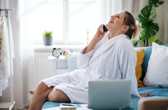 Young woman with telephone and laptop on bed indoors at home in the morning.