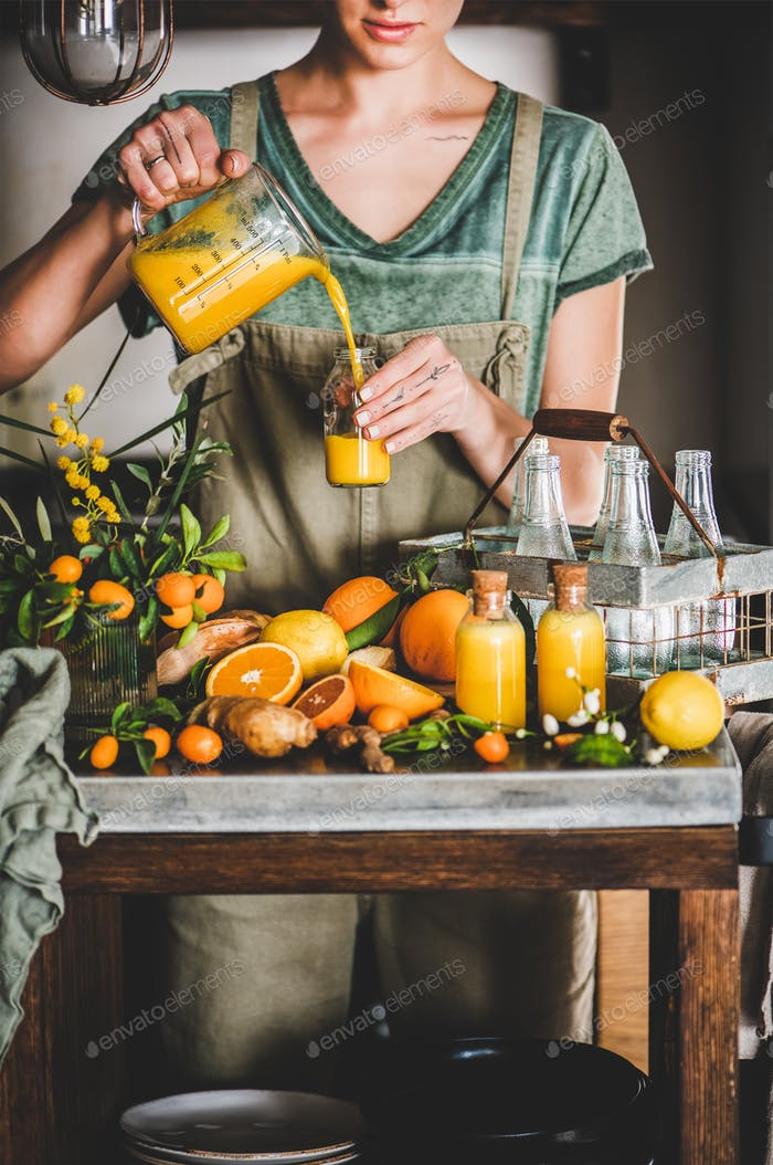 Young woman pouring fruit immune boosting drink to bottle